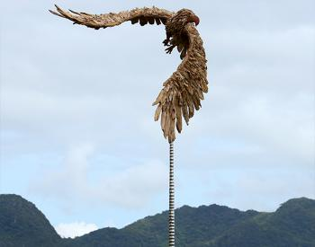 A driftwood and stainless steel sculpture of an Eagle in the turn, mounted on a polished stone base